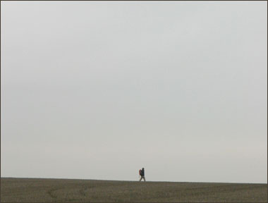 A person walking in the far off distance with a huge sky.