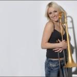 Carol Jarvis smiling holding a trombone.