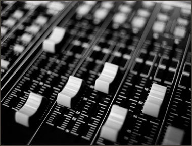 A close-up of faders on a mixing desk.