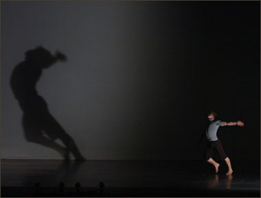 Dark image of a young person dancing while casting a large shadow.