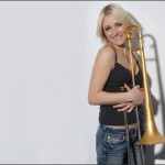 Carol Jarvis smiling holding a trombone.